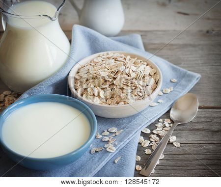 Rolled oats in a bowl and milk on a wooden table