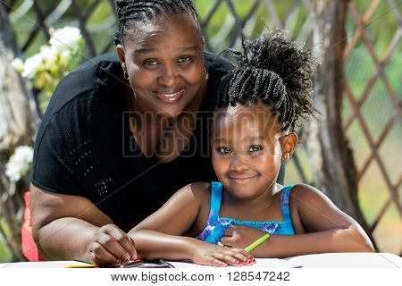 Close up portrait of african mother and little daughter with braided hairstyle in garden.Girl drawing on paper with color pencils outdoors.