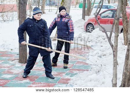 Two boys clean artificial green-red covering of playground with snow shovels.