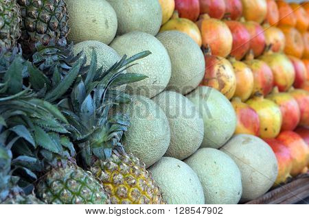 Fruit lying in rows on the counter trading, pineapples, melons, mangoes