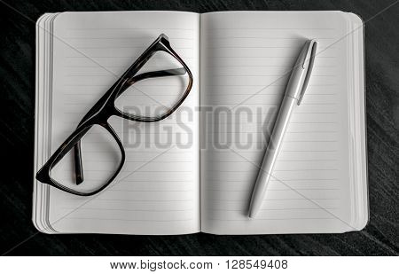 Notebook With Red Bookmark On A Dark Table With A Pen And Glasses