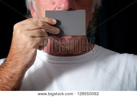 Close up of a man holding a grey card over his mouth against a black background wearing white t shirt. Censorship or freedom of speech concept.