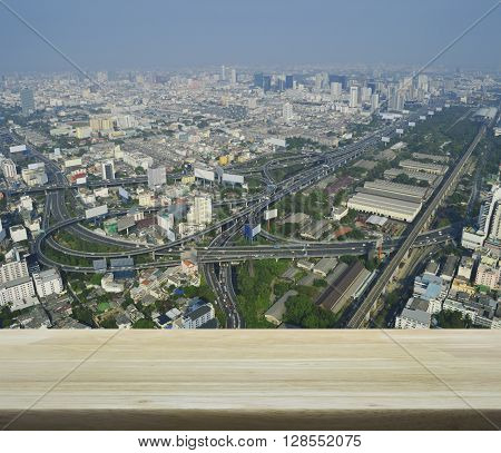Empty wooden table over aerial view of cityscape expressway and highway for your product display montage