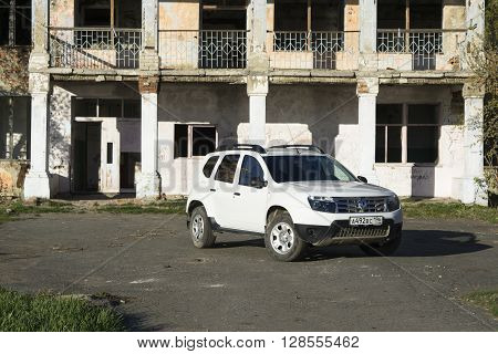 Nizhnyaya Ilenka, Russia - May 02, 2016: White Renault Duster near the old brick building on a summer evening