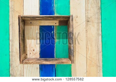 Homemade wooden box shelf on colored wooden wall.