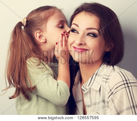 Happy Cute Kid Girl Whispering The Secret To Her Funny Grimacing Mother In Ear In Studio. Toned Clos