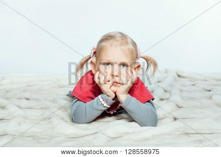 Baby girl with hands on chin is lying down