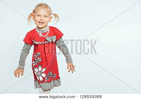 Beautiful baby girl on a white background. Girl goes and grimaces