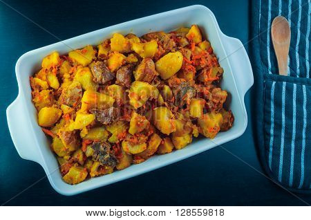 On a black table there is a blue baking dish, potato and meat. A dish ready stewed potato with meat