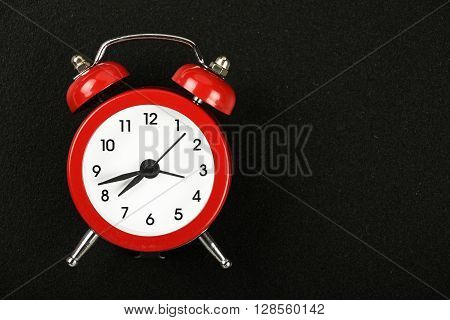 Time concept small red metal alarm clock with red bells over black chalkboard background