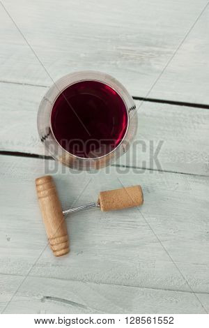 A photo of a glass of red wine with an old wooden bottle opener with a cork shot from above on a teal blue wooden background texture with copyspace