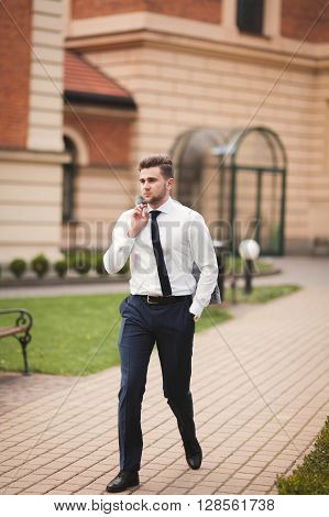 Stylish businessman walking outdoors and looking away.