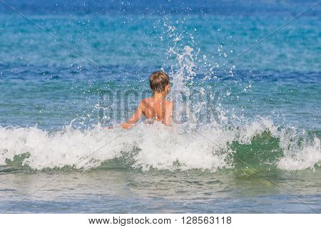 Young boy on the beach  having fun with the waves