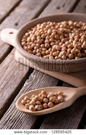 Chickpeas On Wooden Spoon And In Clay Bowl