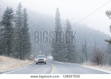 Winter cold weather vehicle icy driving on mountain road with pine trees in snow