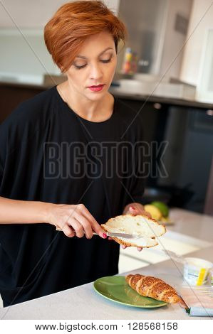 Preparing food. Young woman in kitchen preparing sandwich