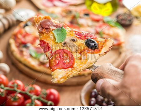 Piece of pizza with mushrooms, ham and tomatoes. Top view.