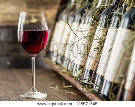 Glass of red wine and wine bottles on the background.