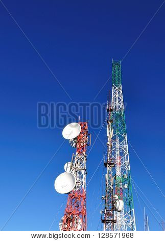 Radio station and communication towers against blue sky vertical image.