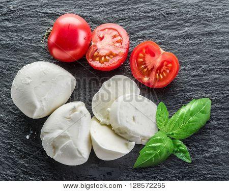 Mazzarella and tomatoes. Dark grey background.