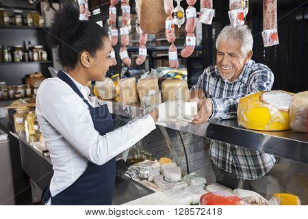 Man Buying Cheese From Saleswoman In Shop