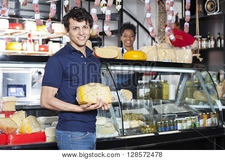 Customer Holding Cheese While Saleswoman Working At Counter