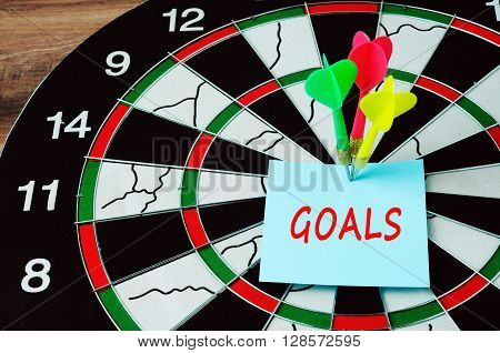 Darts And Bull Eyes With Word Goals On Paper