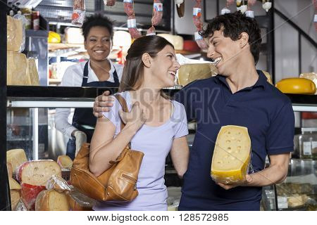 Happy Couple Holding Cheese While Looking At Each Other