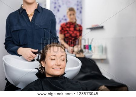 Relaxed Woman Getting Hair Washed In Salon