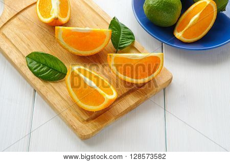Orange segments with leaves on cutting board and white wooden surface