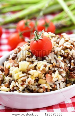 closeup of a bowl with refreshing lentil and rice salad in a table set with a checkered tablecloth
