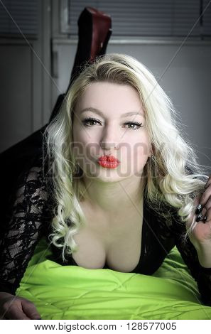 Blond woman resting on green bed and sending mischievous kiss