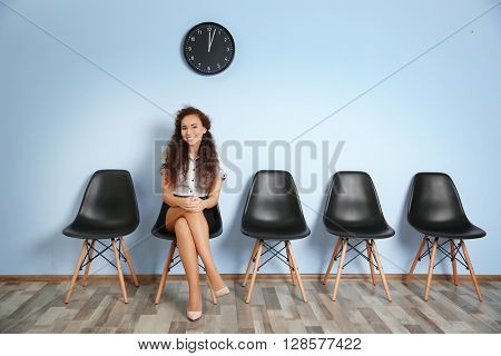 Young woman waiting for interview against blue wall background