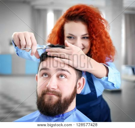 Professional hairdresser making stylish man haircut