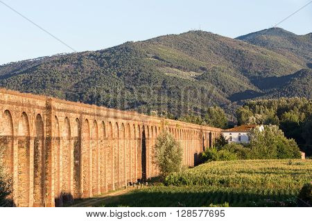 Section of the Nottolini Aqueduct in Tuscany near Lucca Italy leading to the mountains. Warm evening light with classic Tuscan textures and tones. Concepts could include Travel Architecture Europe others.