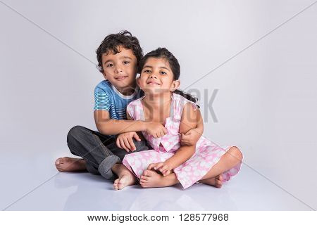 A picture of indian young siblings hugging over white background, asian little siblings hugging