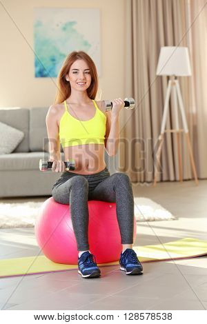 Beautiful young girl doing exercises with dumbbells and fit ball at home