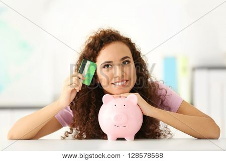 Beautiful young girl with piggy bank and credit card in office