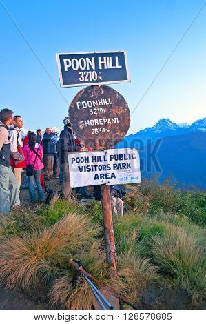 POON HILL, NEPAL - OCTOBER 12, 2008: Poon hill altitude sign Nepal. Tourists meet the sunrise at top of Poon Hill in Himalayas