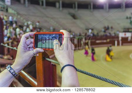 Unrecognizable person taking video of corrida performance