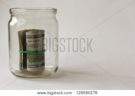 banknotes of 100 dollars in the opened jar