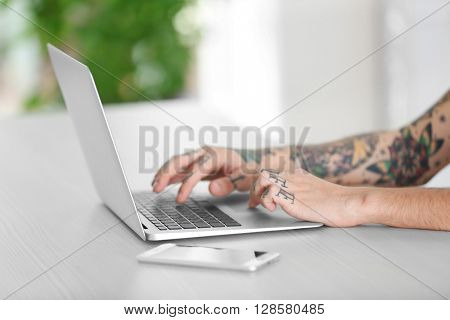 Young man with tattoo using laptop at the table