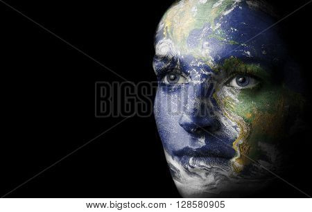 Womans face painted with coloure of mother earth