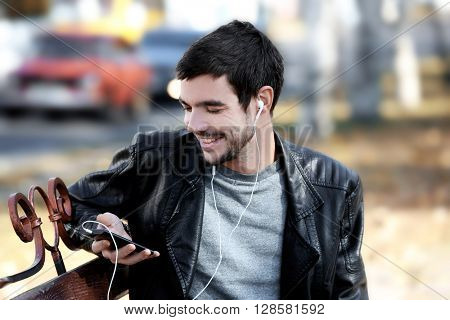 Young man sitting on a bench in park and listening to music