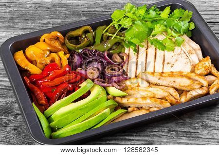 Delicious Chicken Fajita Platter with Avocado Bell Pepper Red Onion and Cilantro close up