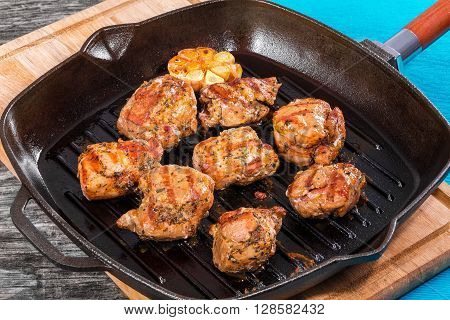 Hot delicious pieces of grilled meat on a skillet on a cutting board on a rustic table close-up