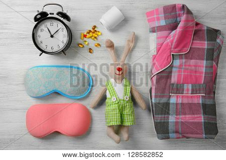 Insomnia concept. Sleeping accessories on wooden table, top view