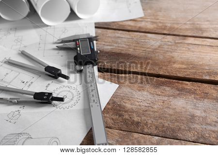 Set of engineering drawings with tools on wooden background