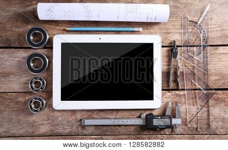 Engineering drawing with tools and tablet, top view