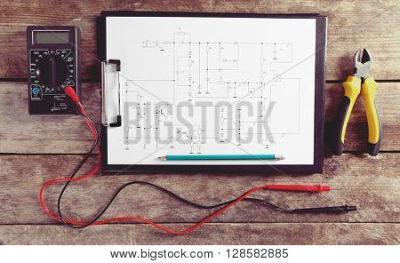 Electrical drawing with tools on wooden table, top view